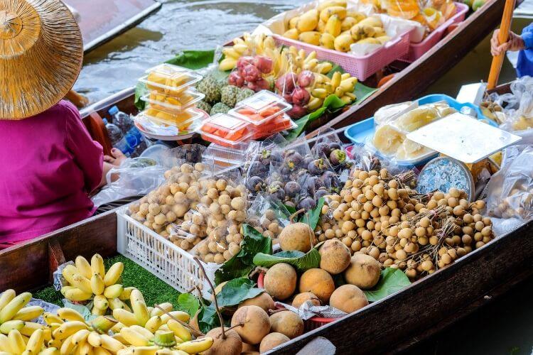 woman on long tail boat selling fruit at damnoen saduak floating market